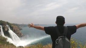 Turysta z plecakiem, stoi ręki szeroko rozpościerać w różnych kierunkach blisko pięknych siklaw na stromym zbiory wideo