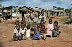 Turysty Europejskie pozy z lokalnymi dziećmi na wiejskiej drodze w małej wiosce w afryki środkowej republice Zdjęcie Royalty Free