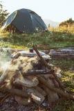 Turysty obóz z ogieniem, garnkiem, namiotem i łupką, obrazy stock