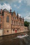 Turystyczna łódź i ceglani domy na kanałowym ` s ostrzymy przy Bruges Obrazy Royalty Free