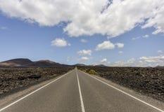 Turystyczna droga przez osamotnionego ciemnego powulkanicznego lawa krajobrazu Timanfaya park narodowy, Lanzarote, wyspy kanaryjs obrazy stock