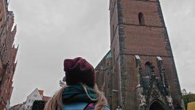 Turystyczna dziewczyna bada z plecakiem biorąc pod uwagę widok i Antyczny katolicki kościół czerwona cegła Niemcy zbiory