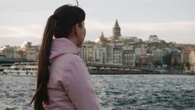 Turystyczna dziewczyna siedzi blisko rzecznej cieśniny i cieszy się bardzo pięknego widok krajobrazowy miasto Domy, widoki zbiory