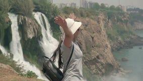 Turystyczna dziewczyna w kapeluszu i plecaku za jej stojakami przed siklawą z ona ręki rozprzestrzenia szerokiego zdjęcie wideo