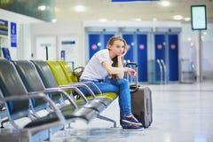 Turystyczna dziewczyna w lotnisku międzynarodowym, czeka jej lot, przyglądający spęczenie zdjęcie royalty free