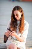 Turystyczna dziewczyny dosłania wiadomość smartphone na wakacjach letnich Młoda atrakcyjna kobieta z telefonem komórkowym outdoor Zdjęcia Royalty Free