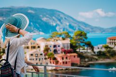 Turystyczna kobieta jest ubranym błękitnych sunhat i bielu ubrania cieszy się widok kolorowa spokojna wioska Assos na słonecznym  fotografia stock