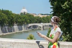 Turystyczna kobieta trzyma pastylkę i patrzeje w kwiatów sundress Rzym Tiber most i arcydzieło kopułę Zdjęcia Stock