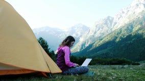 Turystyczna kobieta używa laptop w naturze, freelancer pisać na maszynie na komputerze blisko namiotu w podróży przeciw tłu zbiory
