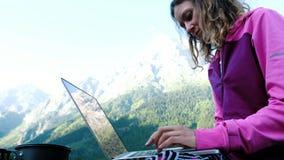 Turystyczna kobieta używa laptop w naturze, freelancer pisać na maszynie na komputerze w podróży przeciw tłu góra zbiory