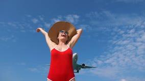 Turystyczna kobieta w czerwonym swimsuit i kapeluszu wita samolot dla podróży Cześć wakacje pojęcie zbiory