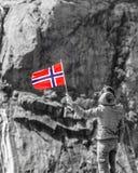 Turystyczna kobieta z norweg flagą w skał górach zdjęcia stock