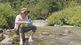 Turystyczna mężczyzna plombowania butelka w halnym riverand pije podczas gdy lato wycieczka zdjęcie wideo