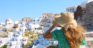 Turystyczna podróżnik dziewczyna w Oia, Santorini wyspa w Grecja Europa podróży wakacje kobieta trzyma jej cieszyć się i kapelusz obrazy stock