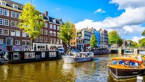 Turystyczne Kanałowe łodzie cumuje przy Anne Frank domem przy Prinsengracht książe kanałem w Jordaan sąsiedztwie w Amsterdam obrazy royalty free
