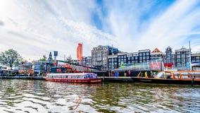 Turystyczne kanałowe łodzie w Damrak kanale w historycznym centrum Amsterdam obrazy stock