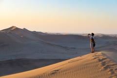 Turystycznego mienia mądrze telefon, brać przy scenicznymi piasek diunami iluminować zmierzchu światłem w Namib pustyni fotografi Zdjęcia Stock