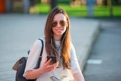 Turystycznej dziewczyny słuchająca muzyka smartphone na wakacjach letnich Młody atrakcyjny turysta z telefonem komórkowym outdoor fotografia stock