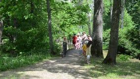 Turystyczni ludzie z dziećmi chodzą drewnianego most w parku zbiory