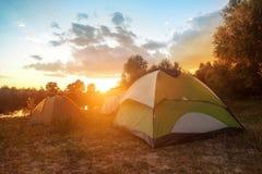 Turystyczni namioty przy riverbank w lesie w lato ranku Zdjęcie Stock