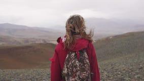 Turystyczni spacery przez gór w dolewaniu padają podróżnik dziewczyna z plecakiem widok z powrotem zbiory