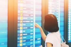 turystyczni Sprawdza loty od monitoru w lotnisku fotografia royalty free