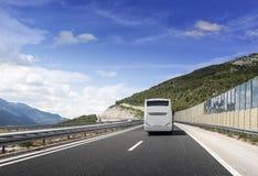 Turystyczny autobus śpieszy się wzdłuż kraj szybkościowej autostrady przeciw tłu halny krajobraz Fotografia Stock