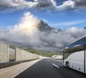Turystyczny autobus śpieszy się wzdłuż kraj szybkościowej autostrady przeciw tłu halny krajobraz Zdjęcie Stock