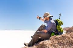 Turystyczny backpacker siedzi halnego szczyt nad soli pustynia, Boliwia Obraz Royalty Free