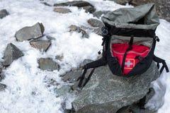 Turystyczny czarny plecaka lying on the beach przy śniegiem i kamieniem Zdjęcia Royalty Free