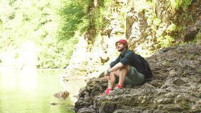 Turystyczny facet siedzi blisko jeziora w dzikim lata drewnie z plecakiem wyprawa zdjęcie wideo