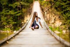 Turystyczny kobieta spacer drewnianym zawieszenie mostem nad rzeka fotografia royalty free