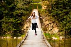 Turystyczny kobieta spacer drewnianym zawieszenie mostem nad rzeka obrazy royalty free