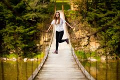 Turystyczny kobieta spacer drewnianym zawieszenie mostem nad rzeka obraz stock