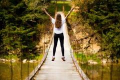 Turystyczny kobieta spacer drewnianym zawieszenie mostem nad rzeka zdjęcia royalty free