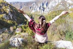 Turystyczny kobiety obsiadanie na wierzchołku jesieni góra, cieszy się widok obrazy stock
