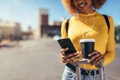 Turystyczny kobiety odprowadzenie na ulicznym patrzeje telefonie komórkowym zdjęcia royalty free