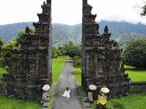 Turystyczny kobiety odprowadzenie przez balijczyk bramy Candi Bentar Wakacje na Bali zdjęcia royalty free