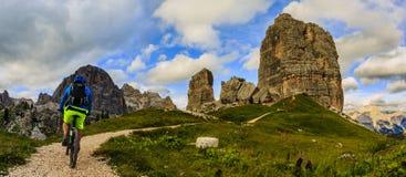 Turystyczny kolarstwo w Cortina d ` Ampezzo, stunning Cinque Torri i obraz royalty free