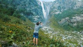 Turystyczny mężczyzna bierze obrazek na smartphone siklawie w górach Technologia w dzikim fotografia royalty free