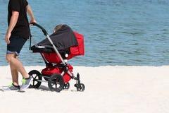 Turystyczny mężczyzna dosunięcia dziecko w spacerowiczu na białej piasek plaży obraz royalty free