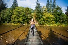 Turystyczny mężczyzna spacer długim drewnianym zawieszenie mostem nad rzeka zdjęcie royalty free