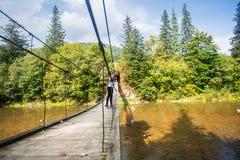 Turystyczny mężczyzna spacer długim drewnianym zawieszenie mostem nad rzeka fotografia stock