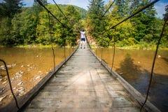 Turystyczny mężczyzna spacer długim drewnianym zawieszenie mostem nad rzeka zdjęcie stock