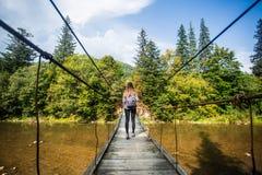 Turystyczny mężczyzna spacer długim drewnianym zawieszenie mostem nad rzeka obrazy royalty free