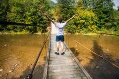 Turystyczny mężczyzna spacer długim drewnianym zawieszenie mostem nad rzeka obrazy stock