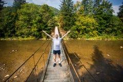 Turystyczny mężczyzna spacer długim drewnianym zawieszenie mostem nad rzeka fotografia royalty free