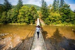 Turystyczny mężczyzna spacer długim drewnianym zawieszenie mostem nad rzeka zdjęcia royalty free