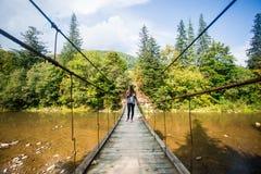 Turystyczny mężczyzna spacer długim drewnianym zawieszenie mostem nad rzeka zdjęcia stock