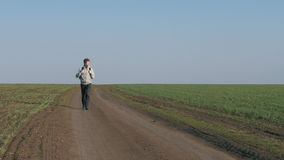 Turystyczny młody męski odprowadzenie w kierunku drogi gruntowej przez zielonego pola dalej zbiory wideo